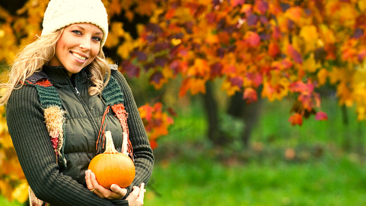 Young blonde woman holding a pumpkin in fall